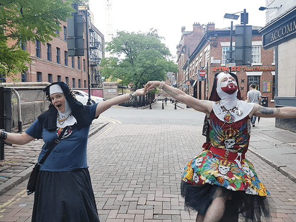 Sister Polly and Sister Judy sitting on the Canal Street rainbow bollards