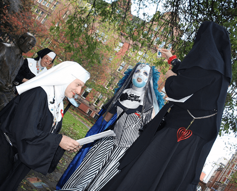 Sister Polly offering cat food to Sister BangBang